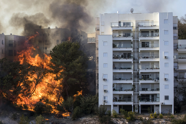 A picture taken on November 24, 2016 shows a fire raging in the northern Israeli port city of Haifa. Hundreds of Israelis fled their homes on the outskirts of the country's third city Haifa with others trapped inside as firefighters struggled to control raging bushfires, officials said. / AFP PHOTO / JACK GUEZ